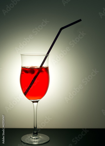 Red cocktail drink with straw backlit, grey background.