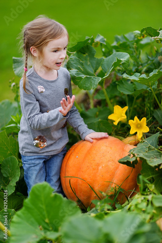 Cute little girl sitting on a pumpkin
