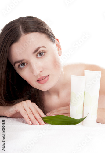 Woman with well-groomed skin near organic cosmetics - isolated o