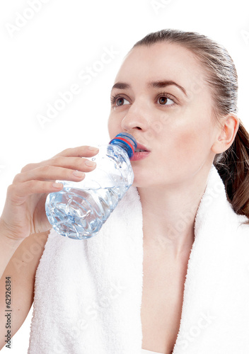 Young woman drinking mineral water bottle, isolated on white bac
