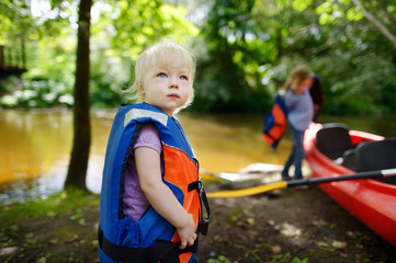 Cute toddler girl getting ready for kayaking