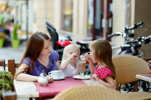 Mother and her daughters relaxing in outdoor cafe