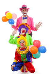 Three people dressed up as colorful funny clowns over white back