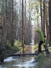 A woman passes a stream on forest backgroun