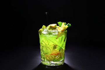 Green cocktail like mojito on dark background