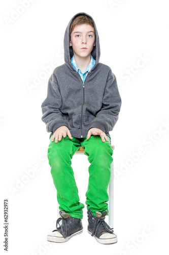 upright sitting male teenager on a stool, isolated on white