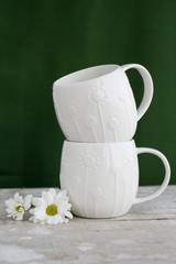 Two white cup on a green background and white flower