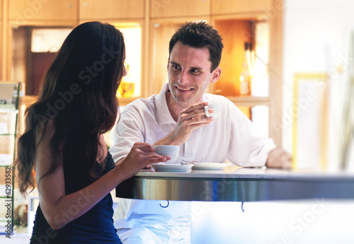 Young couple drinking coffee together in a bar