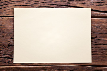 White sheet of paper on old wooden table.