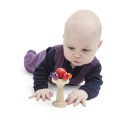baby looking at wooden toy