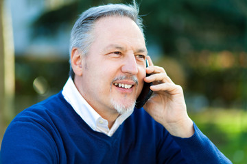 Mature man talking at the phone