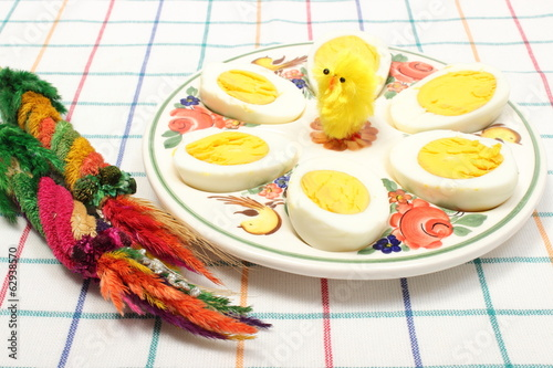 Easter palm and halves of eggs lying on colorful plate