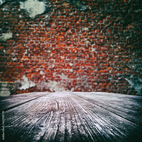 Empty wooden table with old brick wall