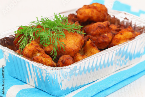 Fried cod pieces in take away tray