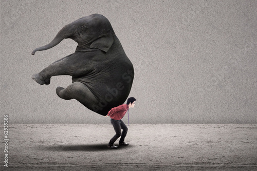 Businessman carry elephant on grey - leadership concept