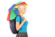 Blond female student walking with umbrella