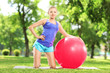 Smiling blond female posing with pilates ball in park