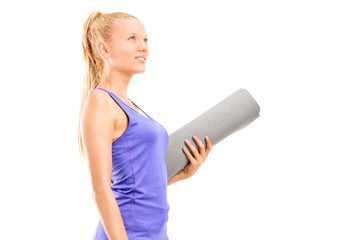 Woman holding an exercise mat and looking up