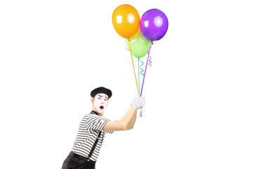 Young mime artist holding balloons and flying