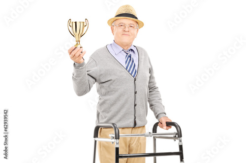 Elderly gentleman with walker holding a gold cup
