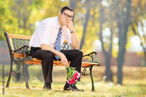Sad young man holding a bouquet of flowers and sitting on bench