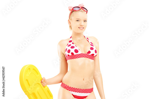 Sexy female in bikini holding a yellow swimming float