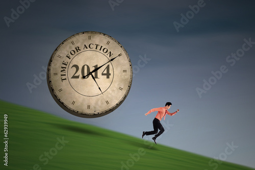 Businessman running with big time clock