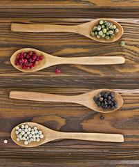 Cuatro cucharas de madera con pimientas de color