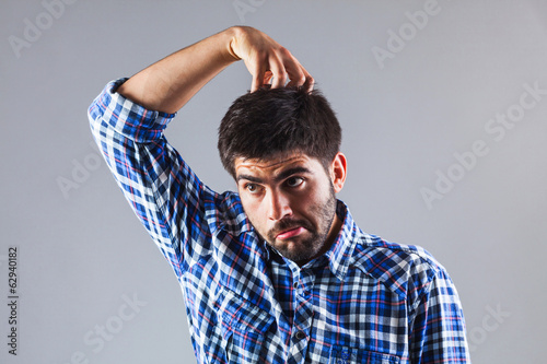 Funny man thinking while scratchin his head