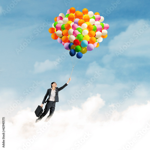 Businesswoman flying with balloons