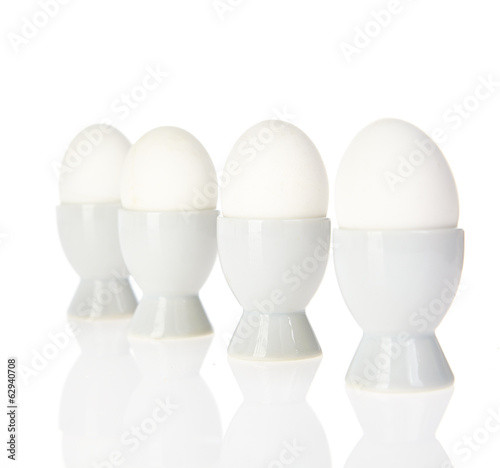 Four white hen's eggs standing vertical on white background