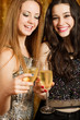 Two beautiful girl friends toasting with champagne