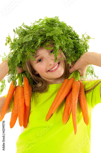 Funny little girl with fresh carrots