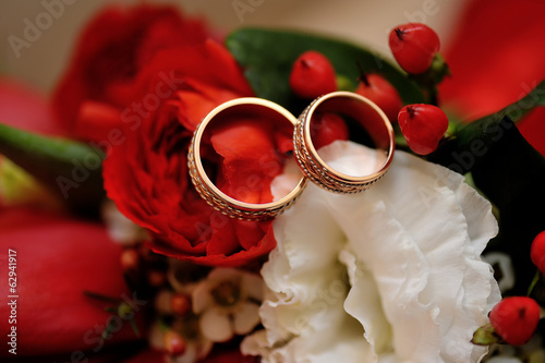 gold wedding rings on a wedding bouquet close up