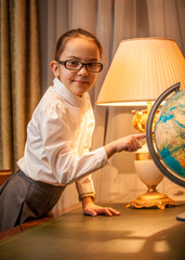 portrait of little girl in eyeglasses pointing at globe on desk