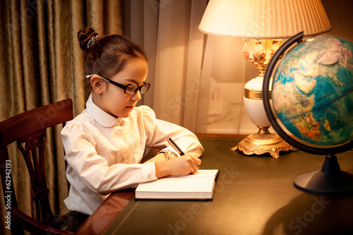 Little girl writing in notebook at desk with lamp and globe