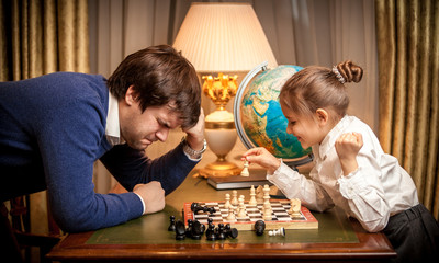 Closeup photo of little girl won chess at man