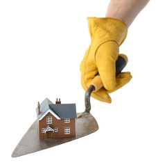 presenting a house on a trowel isolated on a white background