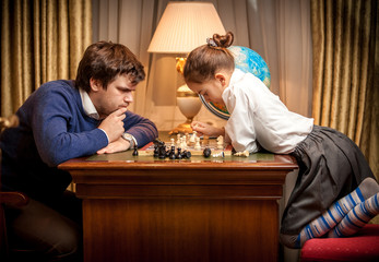 Adult man and smart little girl playing chess