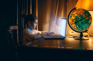 Portrait of little girl doing homework on laptop at evening