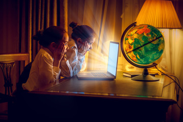 Two little girls looking with amazement at laptop at night