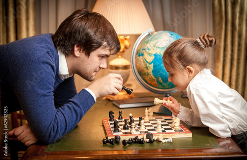 Portrait of handsome man playing chess with girl