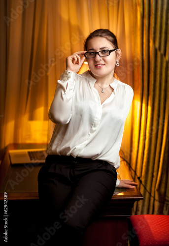 businesswoman in eyeglasses and white blouse sitting on table
