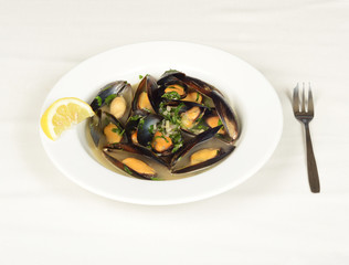 Mussels soup with a piece of lemon.