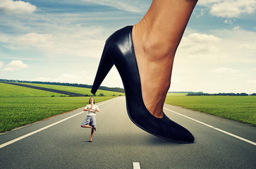 businesswoman standing under big heel