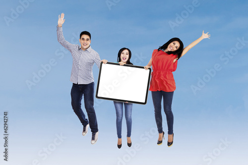Happy friends displaying blank board