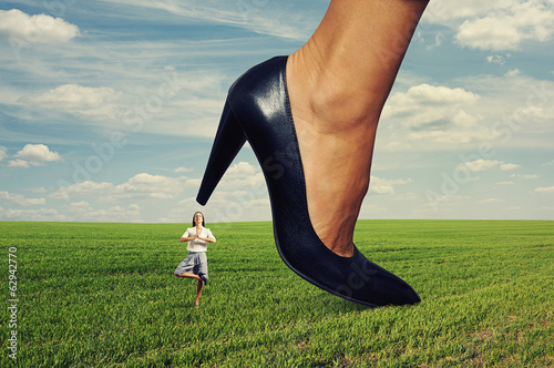 businesswoman under big heel at outdoor