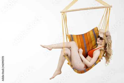 Young woman swinging in hammock on white background