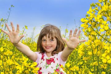 a happy little girl on a field with colza