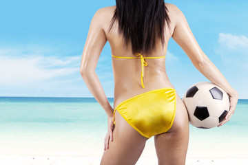 Sexy woman with a soccer ball at beach
